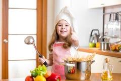 Criança do cozinheiro chefe que prepara o alimento saudável e que mostra o polegar acima Fotos de Stock