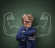 Criança do homem forte que mostra os músculos do bíceps