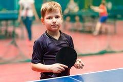 A criança do jogador de tênis está perto de uma tabela do tênis com uma raquete e de uma bola em suas mãos fotos de stock