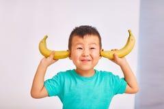 A criança do menino cobriu suas orelhas com as bananas imagem de stock royalty free