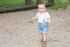 A criança do menino começa a andar e toma suas primeiras etapas no jardim foto de stock