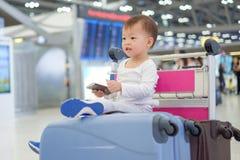 Criança do menino da criança que guarda o passaporte com a mala de viagem, sentando-se no trole no aeroporto foto de stock royalty free