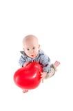 A criança do menino está em uma camisa de manta, um balão vermelho Fotografia de Stock