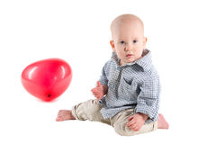 A criança do menino está em uma camisa de manta, um balão vermelho Imagem de Stock Royalty Free