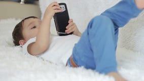 A criança do menino estava encontrando-se um sofá, jogando com um smartphone video estoque