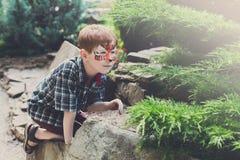 A criança do menino fora joga fora com pintura da cara Fotografia de Stock