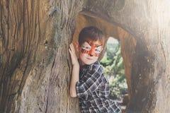 A criança do menino fora senta-se na árvore com pintura da cara Foto de Stock Royalty Free