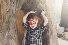 A criança do menino fora senta-se na árvore com pintura da cara Imagem de Stock Royalty Free