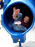 Criança do menino na corrediça da câmara de ar Imagens de Stock