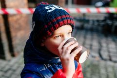 Criança do menino que bebe o cacau quente da caneca de papel Fotografia de Stock Royalty Free