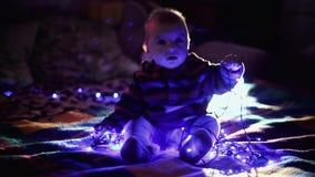 Criança do menino que encontra-se no sofá e na festão escura de observação do azul do fundo dos jogos vídeos de arquivo