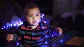 Criança do menino que encontra-se no sofá e na festão escura de observação do azul do fundo dos jogos video estoque