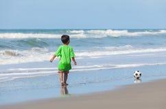 Criança do menino que joga o futebol do futebol na praia imagem de stock royalty free