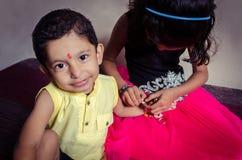 criança do menino que olha a câmera emocionantemente ao sentar-se com seu si Foto de Stock Royalty Free