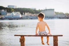 Criança do menino que senta-se em um banco de madeira com sua parte traseira na praia perto da água e que mostra seu sentido da m fotografia de stock royalty free