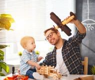 A criança do pai e do filho recolhe o ofício um carro fora da madeira e do jogo fotos de stock