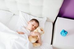 Criança do rapaz pequeno que dorme na cama fotos de stock royalty free