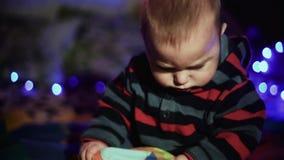 Criança do rapaz pequeno que encontra-se no sofá e na festão de observação do azul dos jogos video estoque