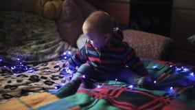 Criança do rapaz pequeno que encontra-se no sofá e nos jogos de observação Festão azul filme