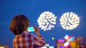 Criança do rapaz pequeno que filma imagens de fogos de artifício bonitos na exposição do céu noturno do telefone celular Mãos da  filme