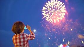 Criança do rapaz pequeno que filma imagens de fogos de artifício bonitos na exposição do céu noturno do telefone celular Mãos da  video estoque