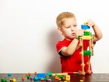 Criança do rapaz pequeno que joga com os brinquedos dos blocos de apartamentos interiores Imagem de Stock Royalty Free