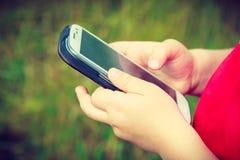 Criança do rapaz pequeno que joga jogos no telefone celular exterior Imagem de Stock Royalty Free