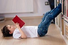 Criança do rapaz pequeno que lê um livro na biblioteca imagem de stock royalty free