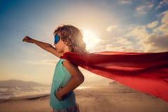 Criança do super-herói na praia Conceito das férias de verão fotografia de stock