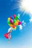 Criança do super-herói que joga com os balões multicoloridos brilhantes Fotografia de Stock Royalty Free