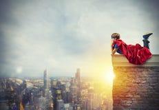 Criança do super-herói que senta em uma parede que sonhos foto de stock royalty free