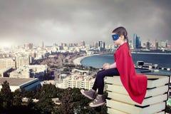 Criança do super-herói que senta-se em uma pilha de livros contra o fundo urbano foto de stock