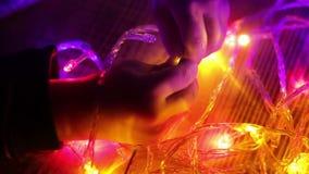 Criança do toque das mãos com luzes na obscuridade, close-up vídeos de arquivo
