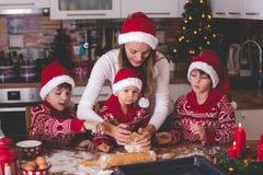 Criança doce da criança e seu irmão mais idoso, meninos, mamã de ajuda que prepara cookies do Natal em casa foto de stock