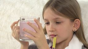 Criança doente com drogas bebendo, comprimidos, cara doente triste da menina com o termômetro no sofá 4K filme