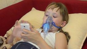 A criança doente no hospital de crianças joga no telefone, tratamento de vapor da inalação do ingaliruut da menina video estoque