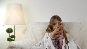 Criança doente que prepara drogas bebendo com água, cara doente triste da menina no sofá filme