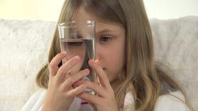 Criança doente que prepara drogas bebendo com água, cara doente triste da menina no sofá 4K filme