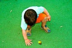 Criança dois anos de jogo velho com uma bola de tênis no playgroun Fotografia de Stock