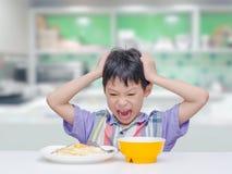 A criança don o ` t quer comer o alimento para o almoço fotografia de stock