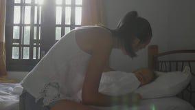 A criança dorme na sala escura A mãe vem, abre as cortinas e acordá-la vídeos de arquivo