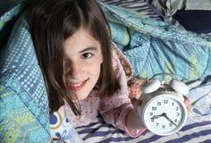 Criança e despertador Fotos de Stock Royalty Free