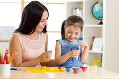 A criança e a mamã fazem pelas mãos que jogam com massa da cor imagens de stock