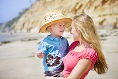 A criança e a matriz jogam na praia junto Fotografia de Stock
