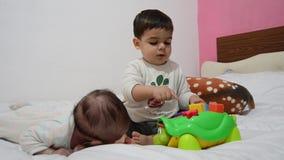 Criança e 2 meses de bebê idoso junto na cama, criança que joga com a tartaruga educacional do brinquedo, bebê que gerencie sobre video estoque