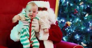 Criança e Santa Claus que sentam-se perto da árvore de abeto de incandescência filme