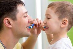 Criança e seus dentes de escovadela do paizinho no banheiro fotografia de stock royalty free