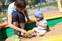 Criança e sua matriz na caixa de areia Fotografia de Stock Royalty Free