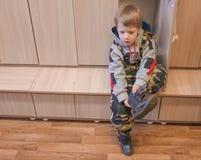 A criança ele mesmo veste-se nos vestiário do kindergar foto de stock