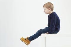Criança elegante em botas amarelas Miúdos da forma rapaz pequeno que senta-se em uma tabela Imagens de Stock